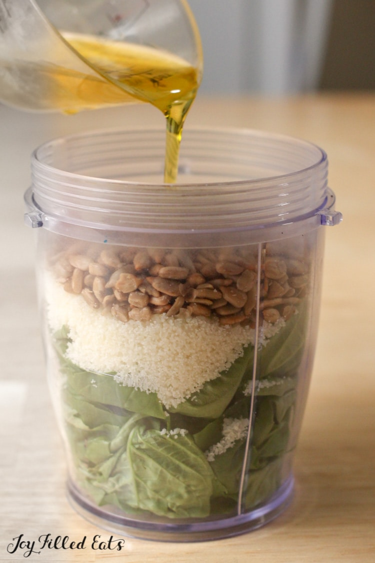 oil being poured over basil, cheese, and sunflower seeds in rocket blender