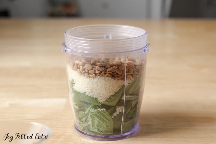 small food processor container with Nut Free Pesto ingredients that include basil, grated pecorino romano cheese and salted sunflower seeds