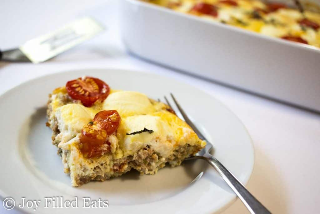 Ricotta & Sausage Breakfast Casserole on a white plate with a fork. Casserole and spatula in the background.