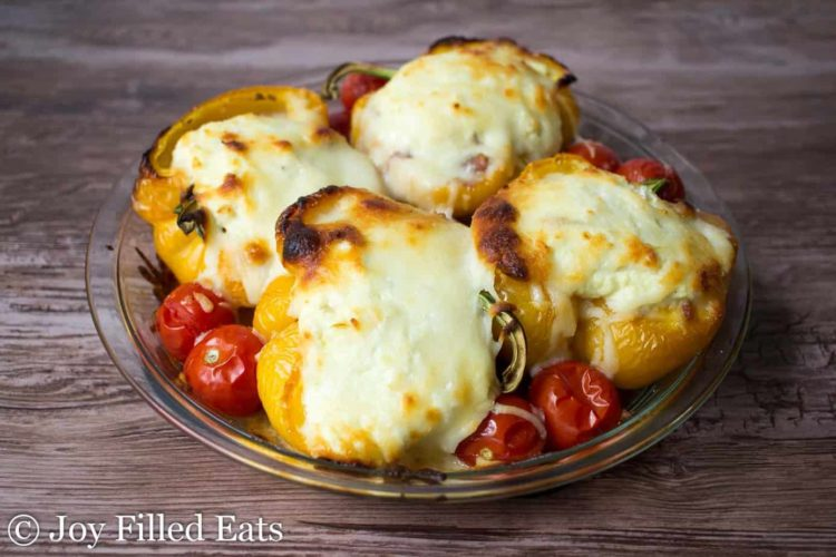 white lasagna stuffed peppers with cherry tomatoes in a pie plate