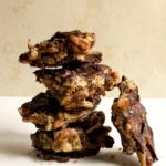 stack of Caramel Pecan Turtle Bark with one piece of candy leaning on the stack
