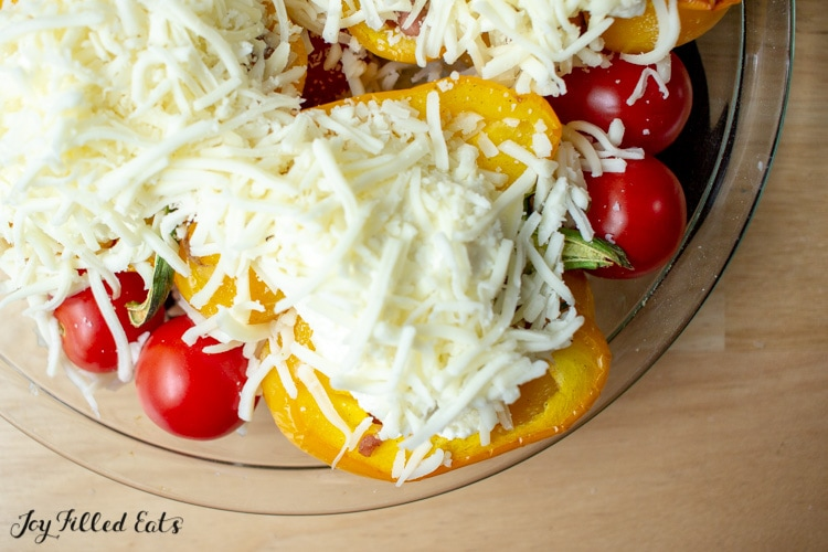 a glass pie plate with tomatoes and keto Stuffed Peppers topped with cheese