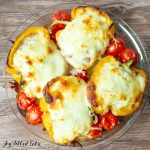 White Lasagna Stuffed Peppers and roasted cherry tomatoes in a glass pie plate on a wood surface