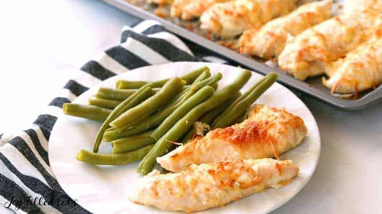 plate with garlic parmesan chicken tenders and green beans set next to a sheet pan lined with garlic Parmesan chicken tenders