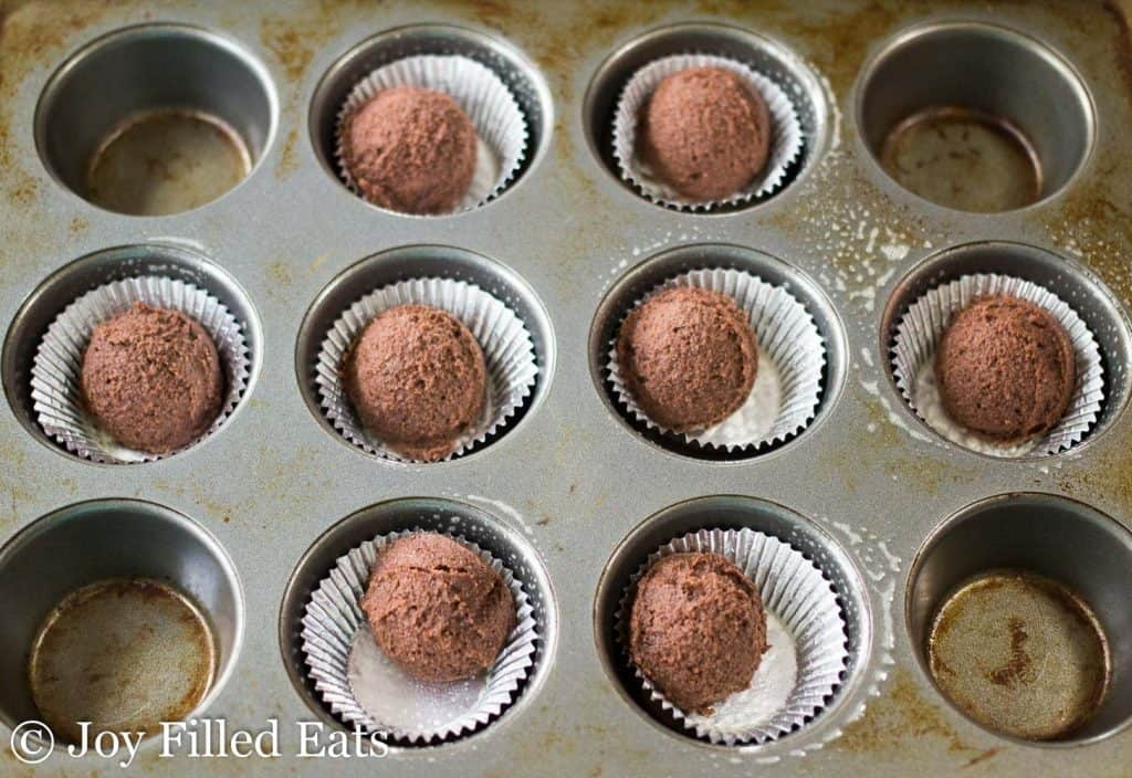 scoops of chocolate dough in lined muffin tins.