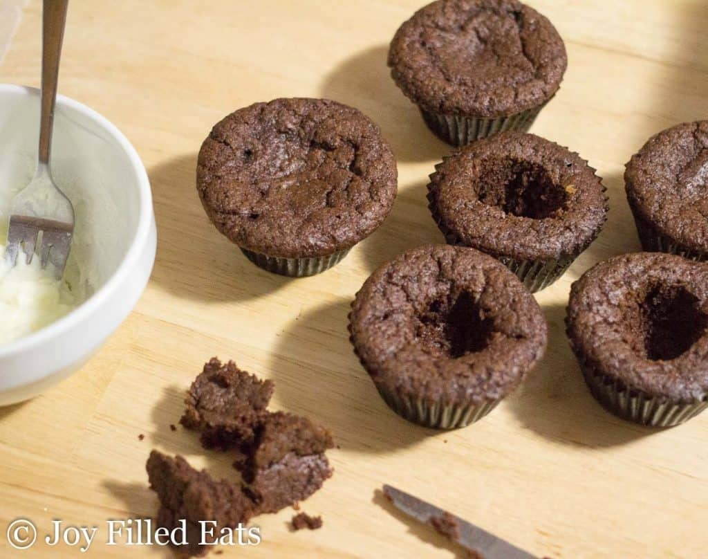 a bunch of dark chocolate cupcakes with center cuts out next to a bowl of peppermint filling
