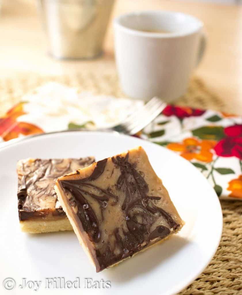 Stacked Salted Caramel Shortbread Squares on a white plate with a cup of coffee and floral napkin