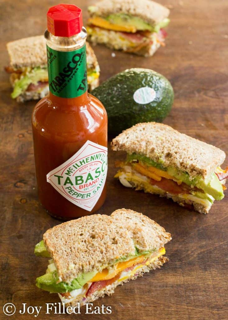 a bottle of Tabasco and whole avocado surrounded by halves of a loaded egg sandwich