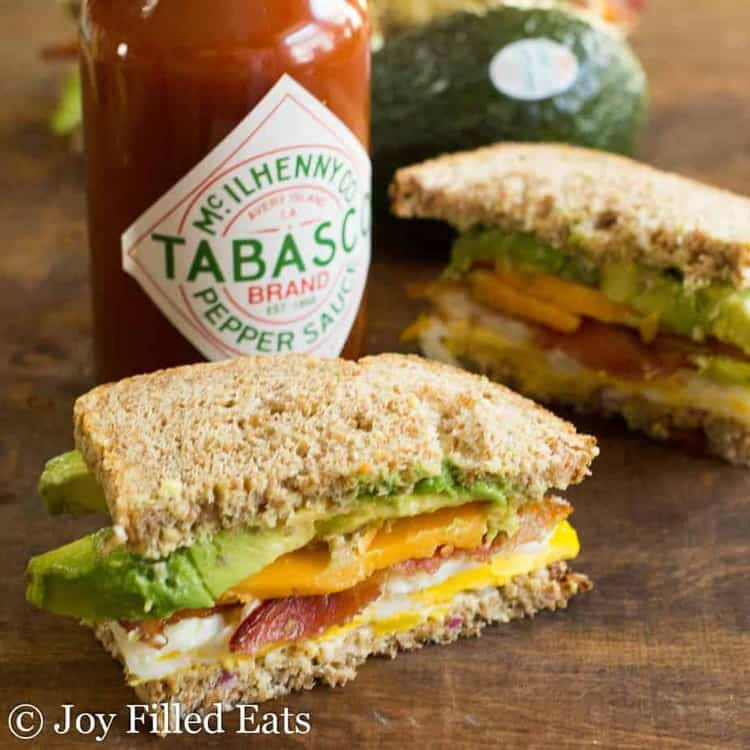 two halves of a loaded egg sandwich placed on a table with a bottle of Tabasco