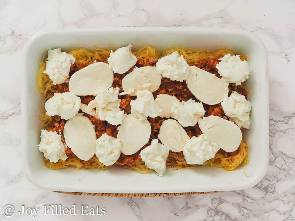 casserole dish of spaghetti squash lasagna topped with dollops of ricotta cheese and slices of mozzarella