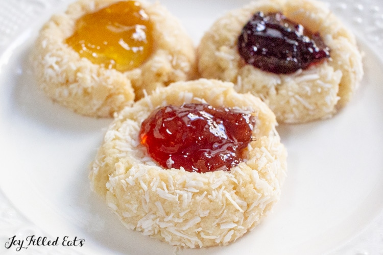 close up on jam thumbprint cookies on parchment paper