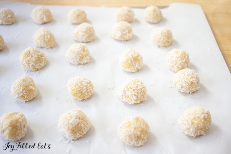 balls of thumbprint cookie dough on parchment paper lined sheet pan