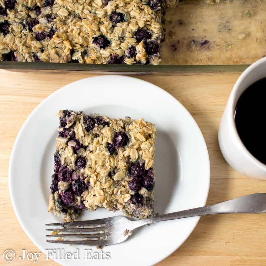 Overhead Close up of Healthy Baked Oatmeal on a white plate with a fork. cup of coffee on the side