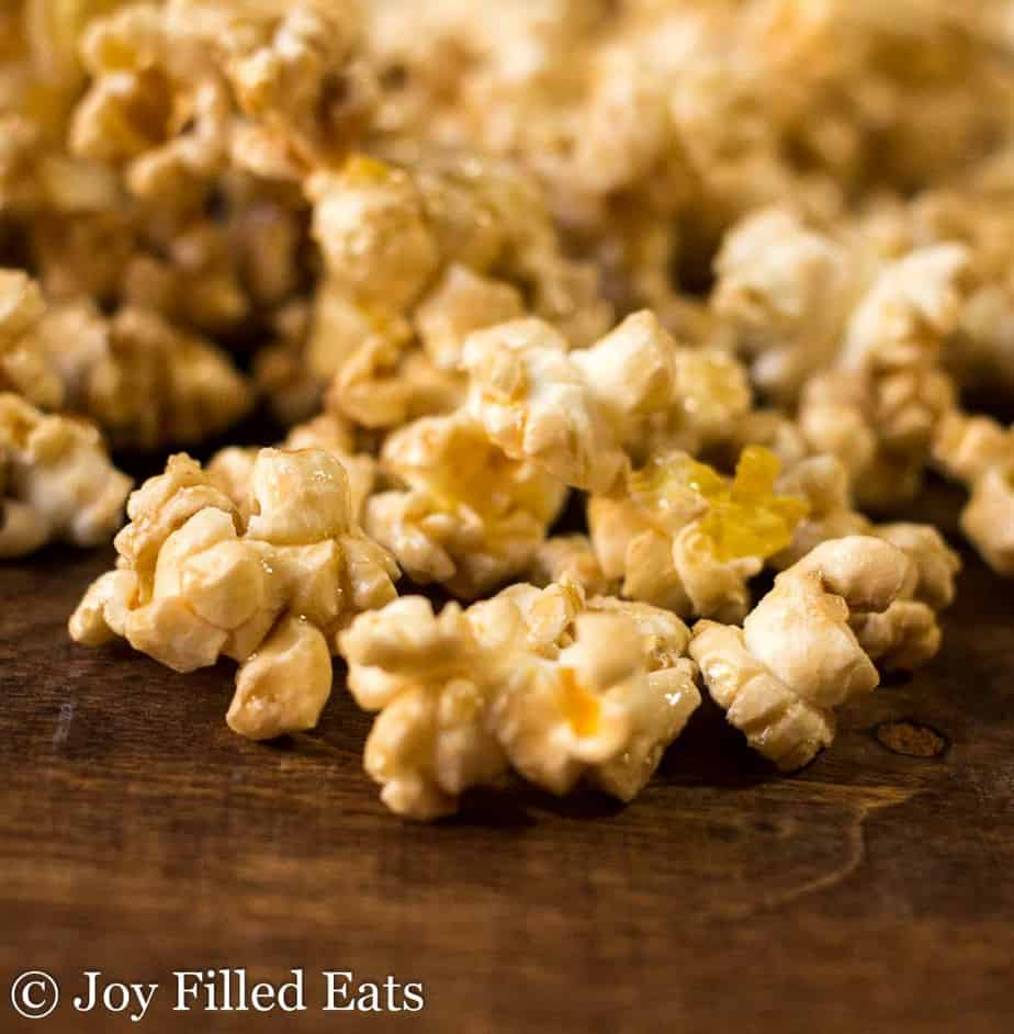 Close up of caramel popcorn on a dark wood cutting board.