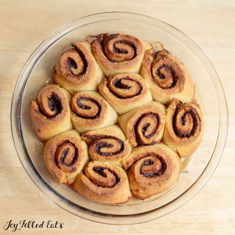 overhead shot of baked uniced cinnamon rolls in a glass pie plate