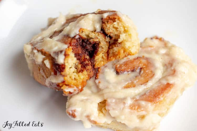 a cinnamon roll with a bite out of it on a white plate