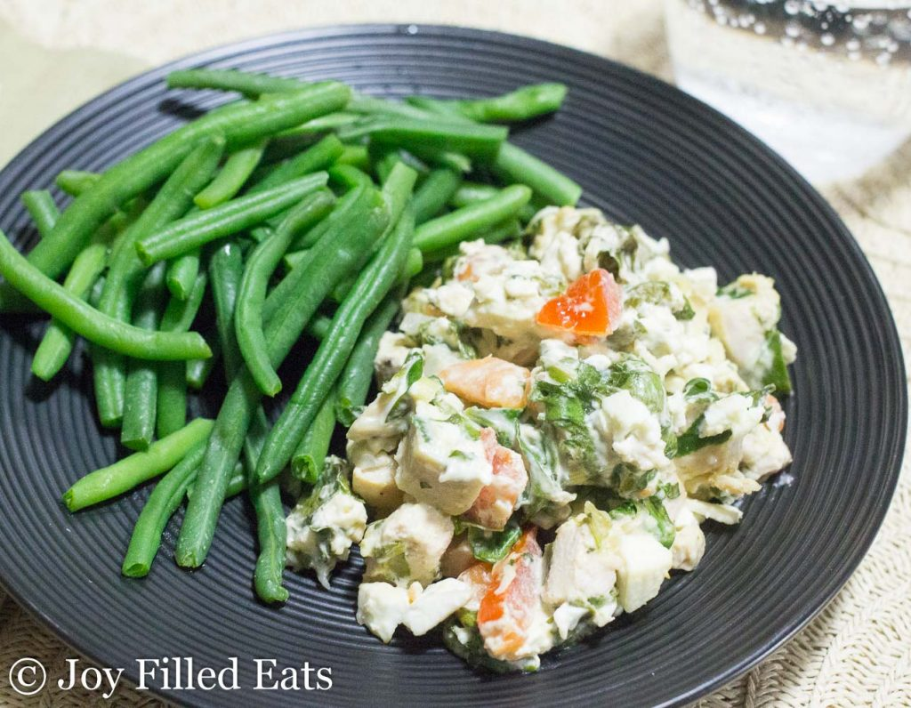 Mediterranean Chicken & Spinach Casserole with a side of green beans on a black plate