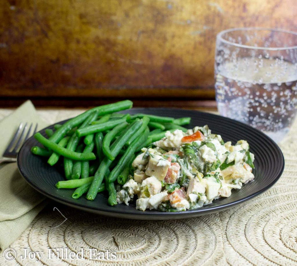 Mediterranean Chicken & Spinach Casserole with a side of green beans on a black plate next to a glass of bubbly water