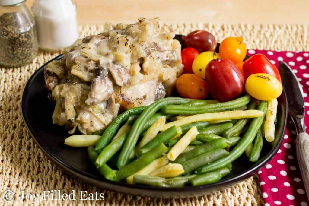 A baked smothered pork chop on a black plate with green beans and tomatoes
