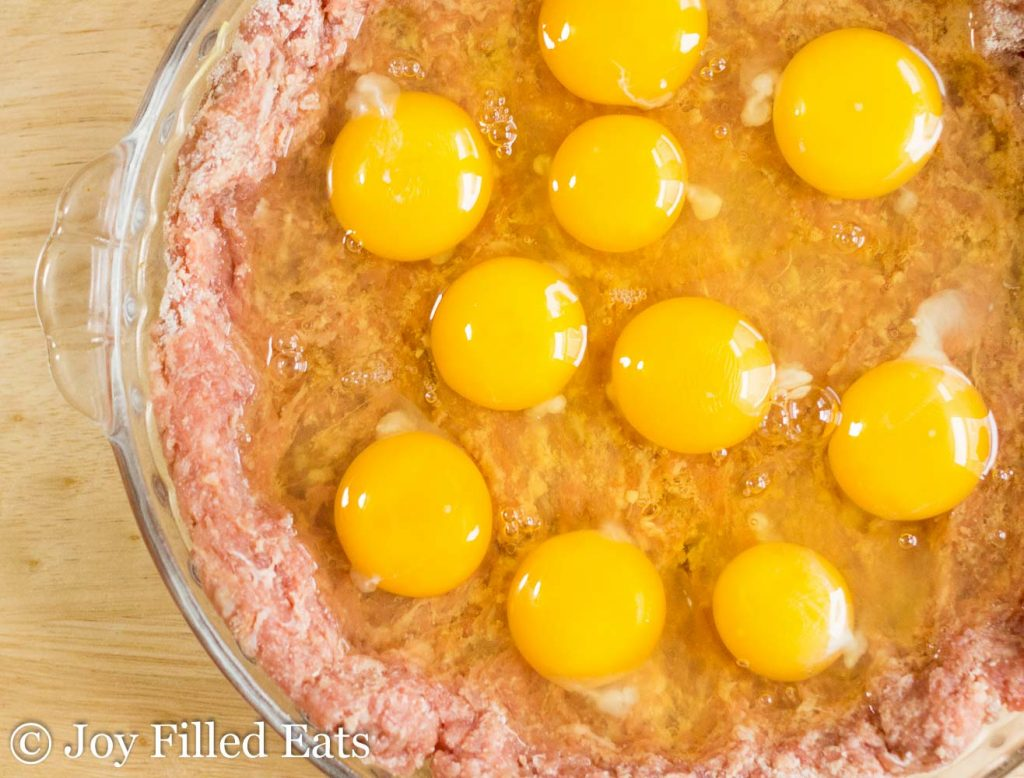Raw eggs cracked on top of the sausage pie.