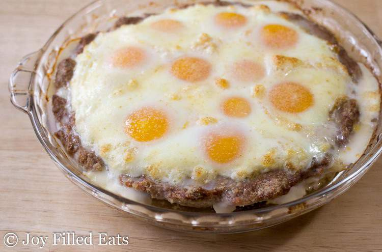 sausage and egg pie in a pie plate before being covered in melted shredded cheese