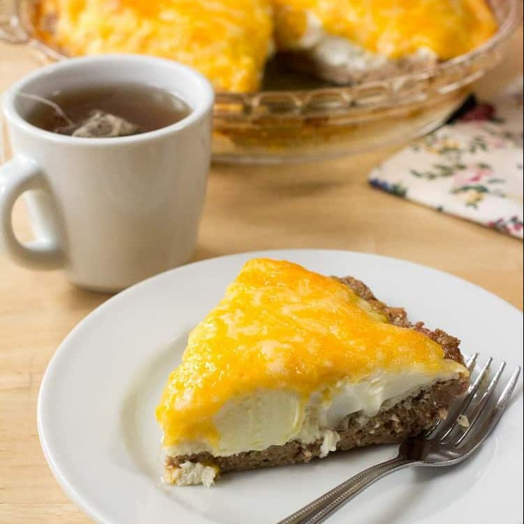 slice of sausage and egg pie on a white plate with fork next to a cup of tea
