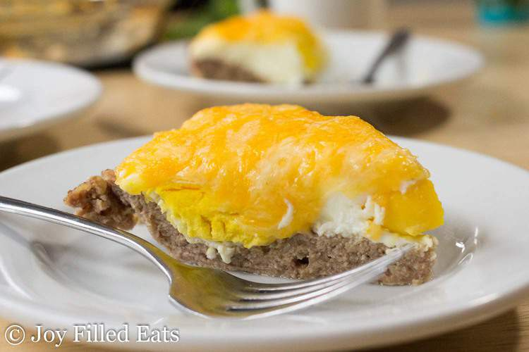 slice of sausage and egg pie on a white plate with a fork