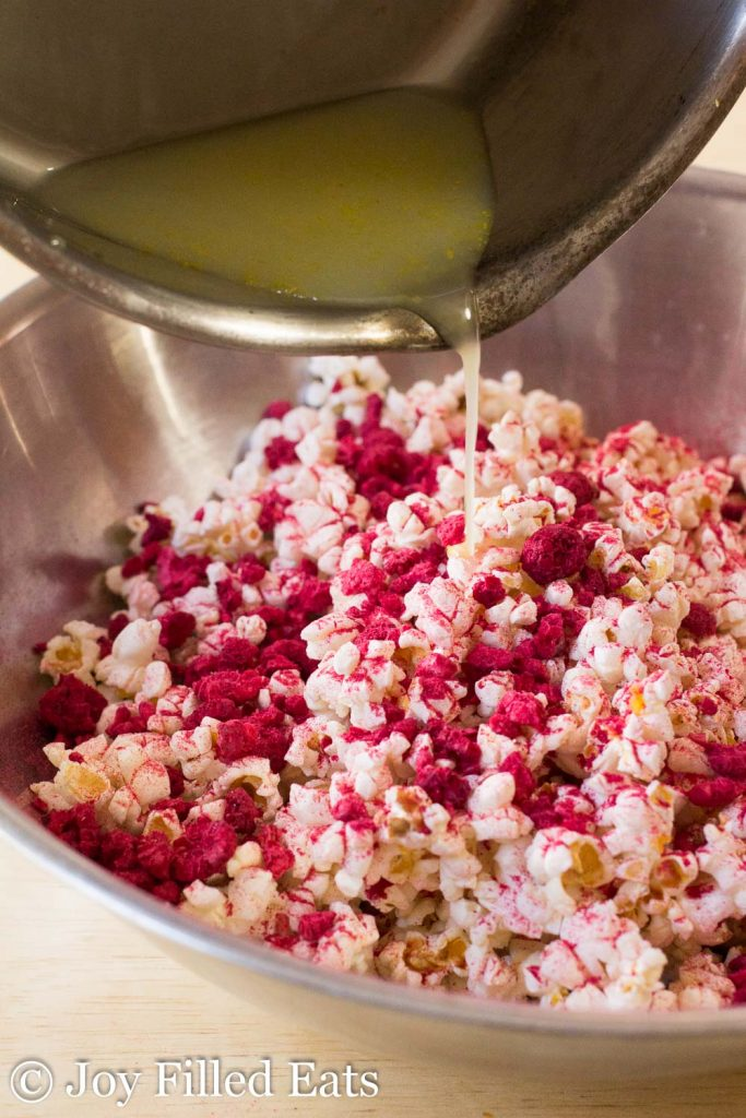lemon sweetener being poured onto raspberry lemonade popcorn