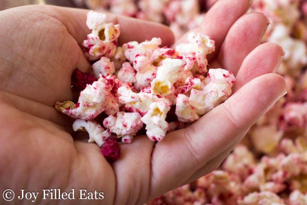 A hand holding some of the raspberry lemonade popcorn