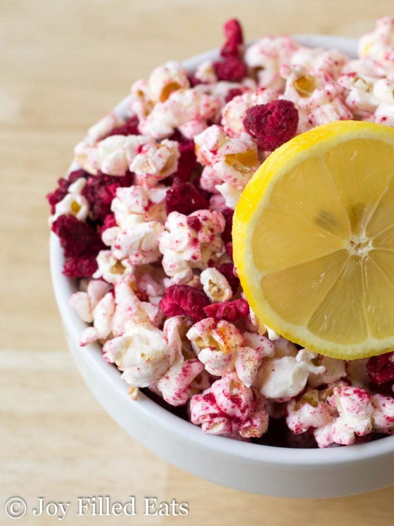 White bowl of raspberry lemonade popcorn with a lemon slice on top