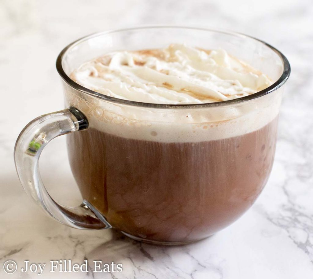 glass mug of sugar free hot chocolate topped with whipped cream