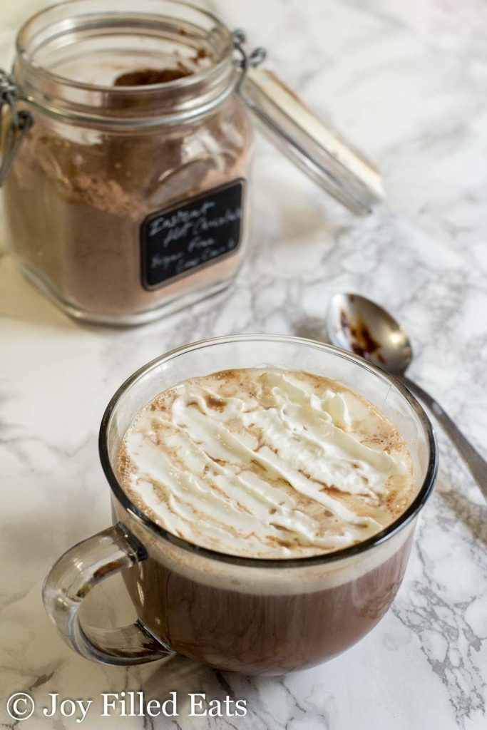 Jar of Sugar Free Hot Chocolate Mix and a mug of whipped cream topped hot chocolate.