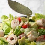 spoon drizzling paleo ranch dressing onto salad close up