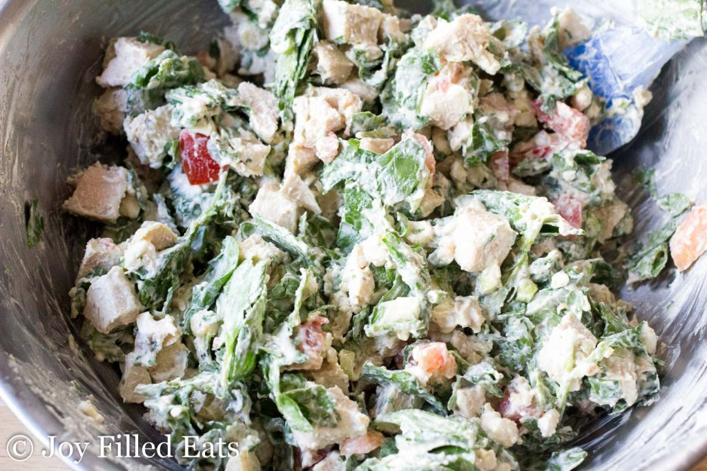 close up on mixing bowl full of Mediterranean chicken and spinach casserole filling