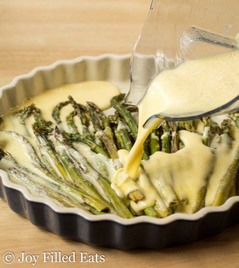 quiche filling being poured onto asparagus lined in a pie plate
