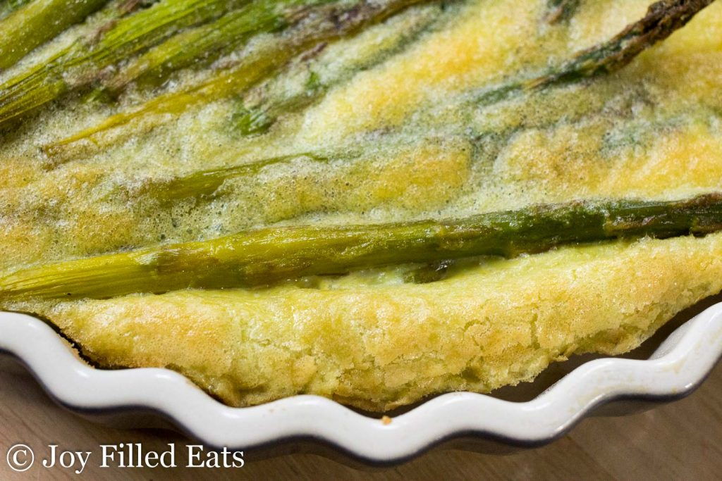 close up on asparagus quiche and pie plate rim