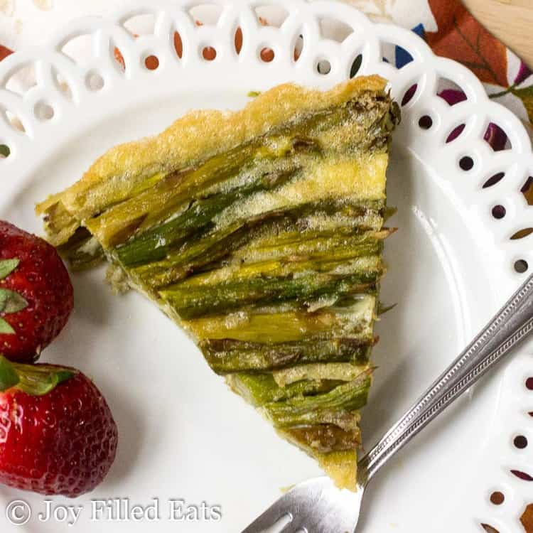 slice of asparagus quiche on a white plate with fork and two whole strawberries from above