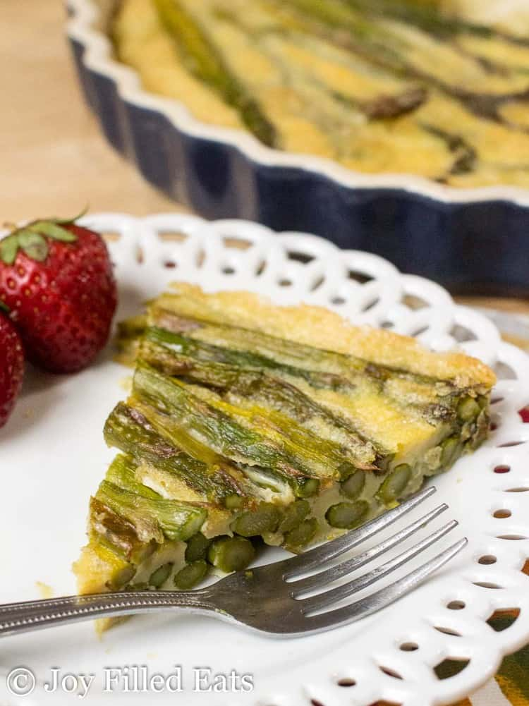 slice of asparagus quiche on a white plate with fork up close
