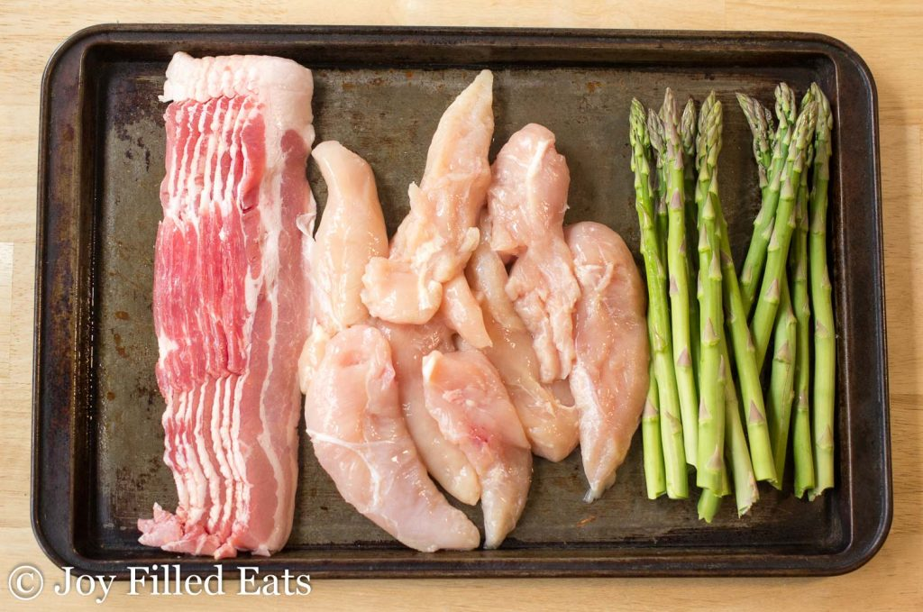 bacon, chicken, asparagus in a baking sheet