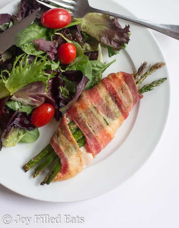 asparagus stuffed chicken wrapped in bacon on a white with a side salad and fork from above