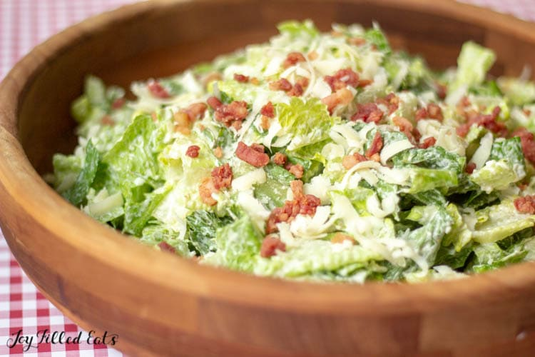large wooden bowl of Caesar salad topped with bacon pieces