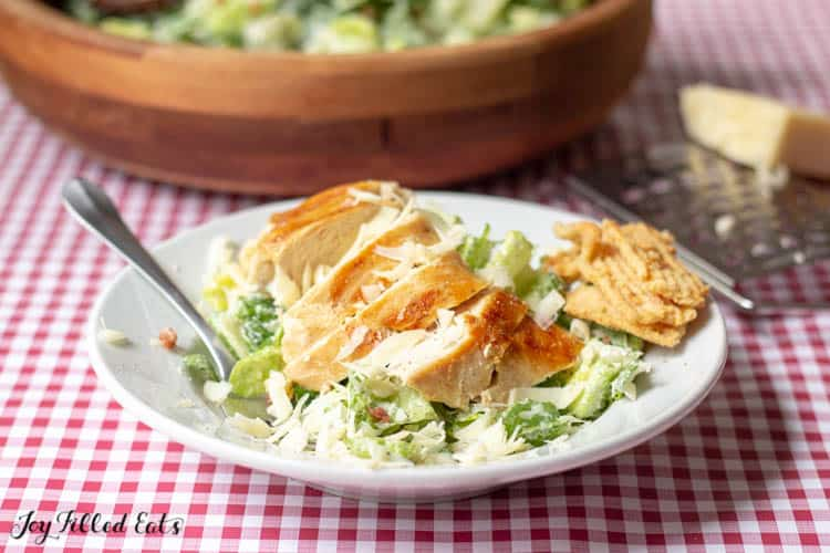 plate of Caesar salad topped with chicken with a fork next to a wooden bowl filled with more Caesar salad