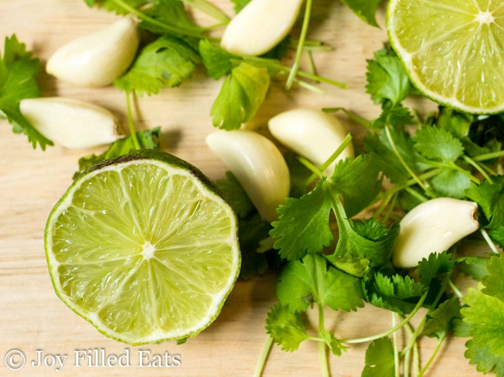 A cut lime, peeled garlic, and cilantro