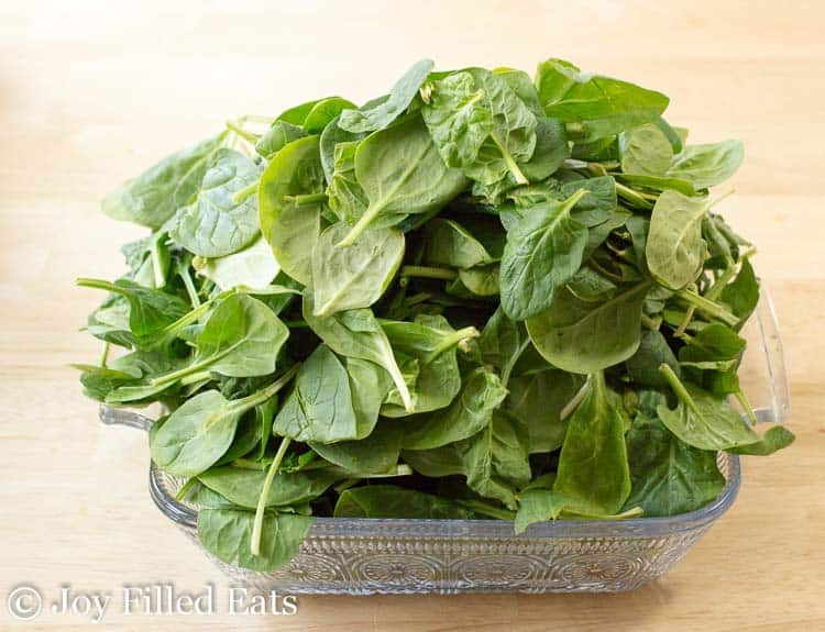 A casserole dish overflowing with raw baby spinach