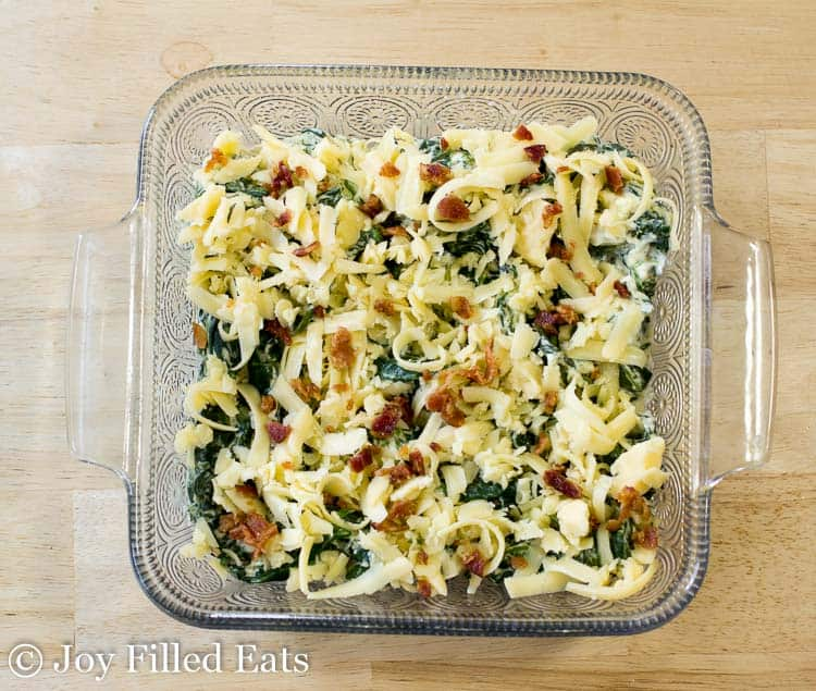 square casserole dish full of creamed spinach topped with shredded cheese and bacon pieces from above