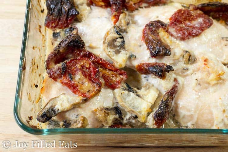 chicken breasts in a baking dish coated in sauce, mushrooms and sun-dried tomatoes close up