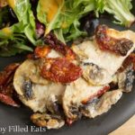 baked chicken breast with mushrooms and sun dried tomatoes on a black plate with a mixed green salad