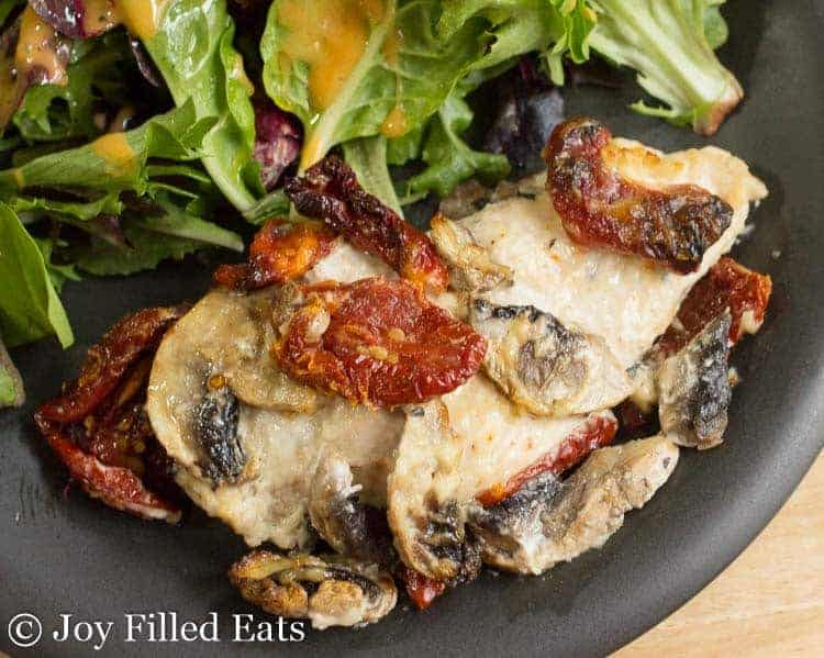 Black plate with baked chicken breast covered with mushrooms and sundried tomatoes