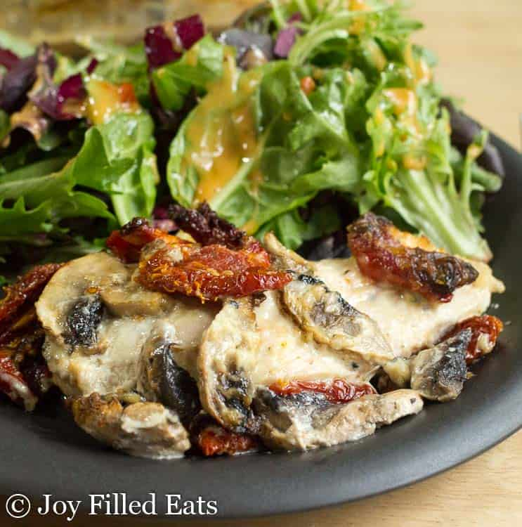 baked chicken breast with mushrooms on a plate with a mixed green salad