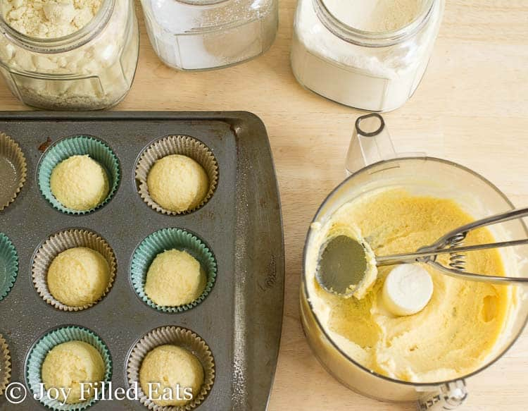wrapper lined muffin tin filled with muffin batter next to food processor of more batter and ice cream scoop